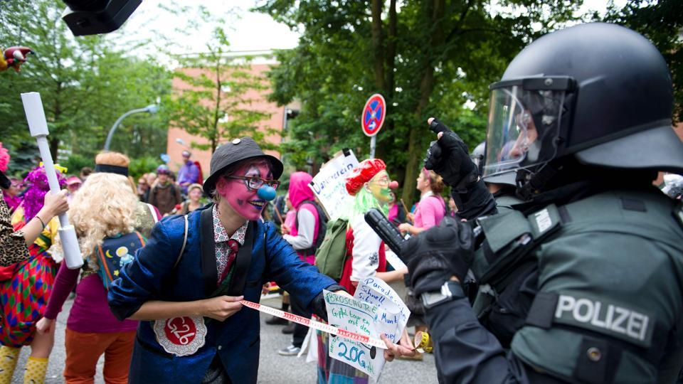 Demonstrators dressed as clowns face policemen as they take part in a protest. Most protesters expressed their opposition to the summit in peaceful ways asking for quick action on climate change and solutions to the migration crisis.  (AFP)