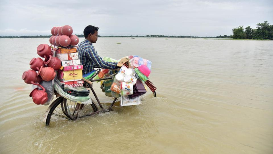 A vendor pushes a bicycle carrying his wares through floodwaters in Balimukh Ashigarh village in Morigoan district. (Biju BORO / AFP)