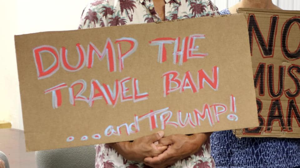 FILE- In this June 30, 2017, file photo, critics of President Donald Trump's travel ban hold signs during a news conference with Hawaii Attorney General Douglas Chin in Honolulu. A federal judge in Hawaii on Thursday, July 6, left Trump administration rules in place for a travel ban on citizens from six majority-Muslim countries.