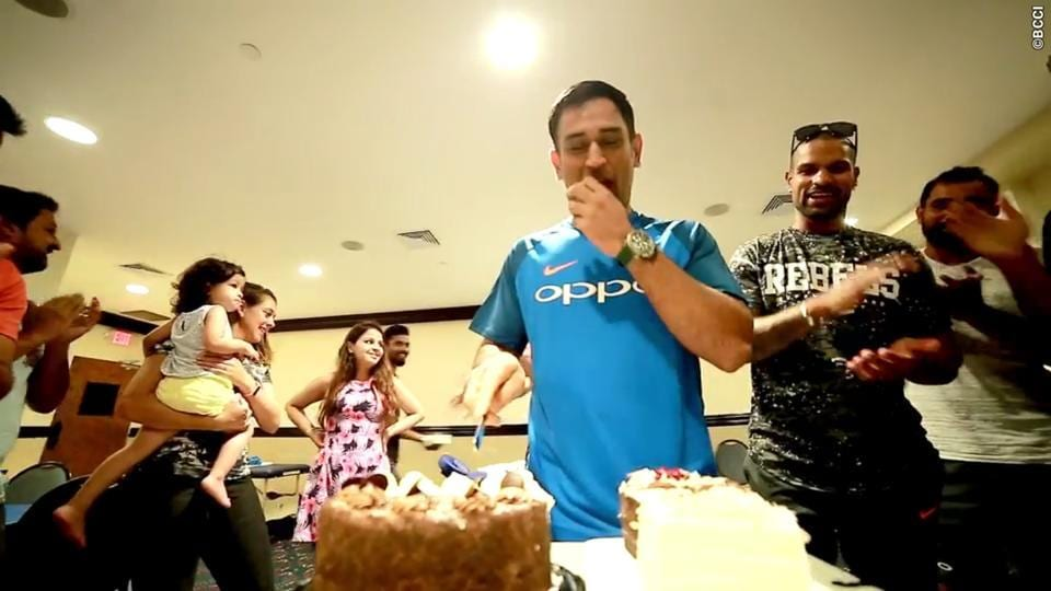 Dhoni is wished by team-mates as he cuts the cake.  (BCCI)