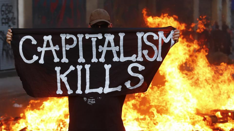 An anti-G20 protester stands in front of a burning street barricade and poses with a flag reading 'Captitalism Kills' in Germany.  (REUTERS)