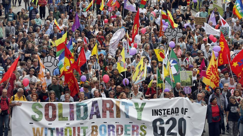 People wave flags during a protest against the G20 summit in Hamburg, Germany, on Saturday.