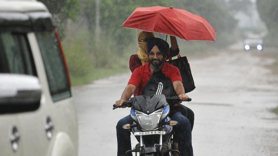 A couple caught unawares in showers at the Industrial Area in Mohali on Friday. Parts of Chandigarh and Mohali witnessed a brief spell of rain in the evening, adding to the humidity.