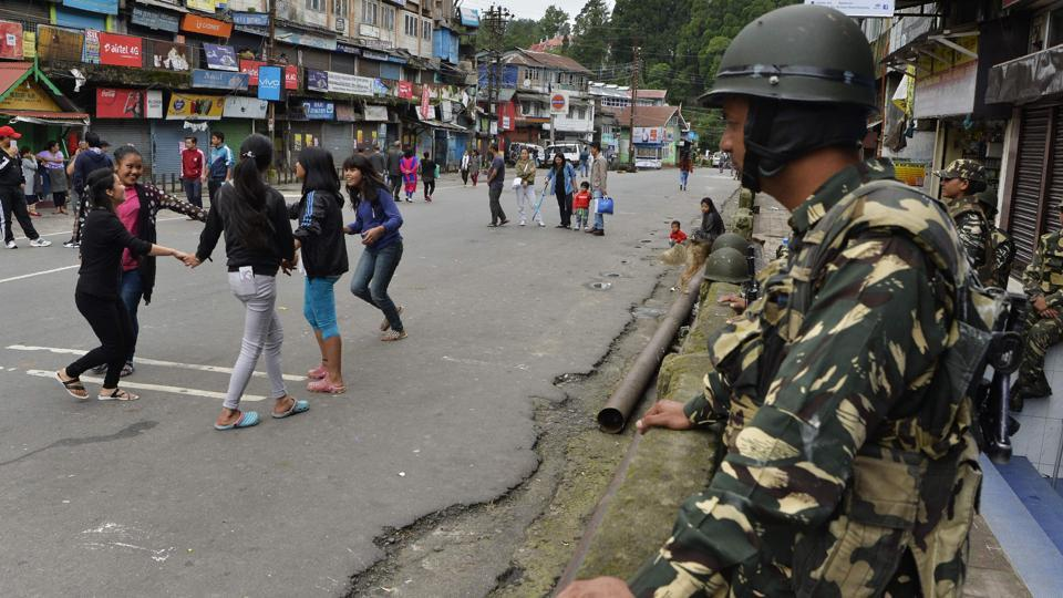 Girls play as paramilitary troops stand guard at Chowkbazar area during an indefinite strike called by the Gorkha Janamukti Morcha in Darjeeling. Photo credit: AFP