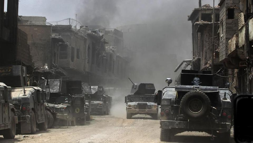 Smoke billows as Iraqi Counter-Terrorism Service (CTS) members advance in the old city of Mosul on July 7, 2017, during the Iraqi government forces' offensive to retake the city from Islamic State (IS) group fighters.