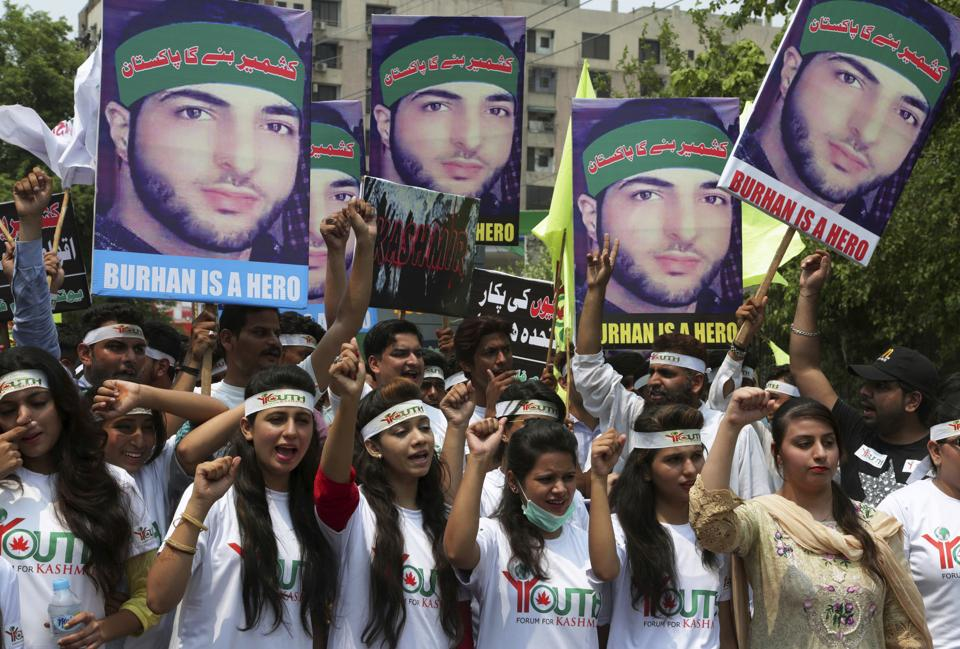 Members of 'Youth Forum for Kashmir' hold posters of Burhan Wani, while chanting anti Indian slogans during a rally to mark the 1st anniversary of his death, in Lahore, Pakistan, on July 8, 2017.