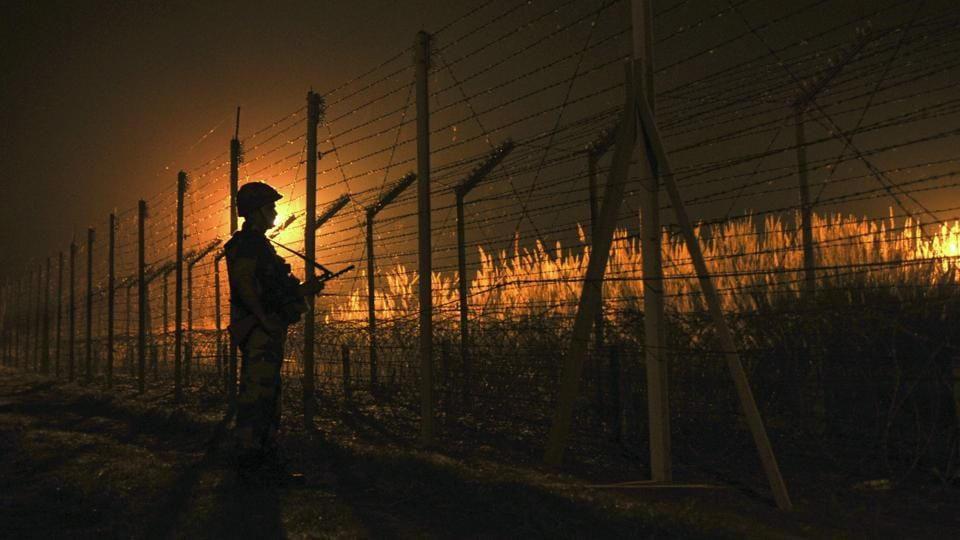 Border Security Force (BSF) soldier standing guard during a night patrol near the fence at the India-Pakistan International Border at the outpost of Akhnoor sector, about 40 km from Jammu.