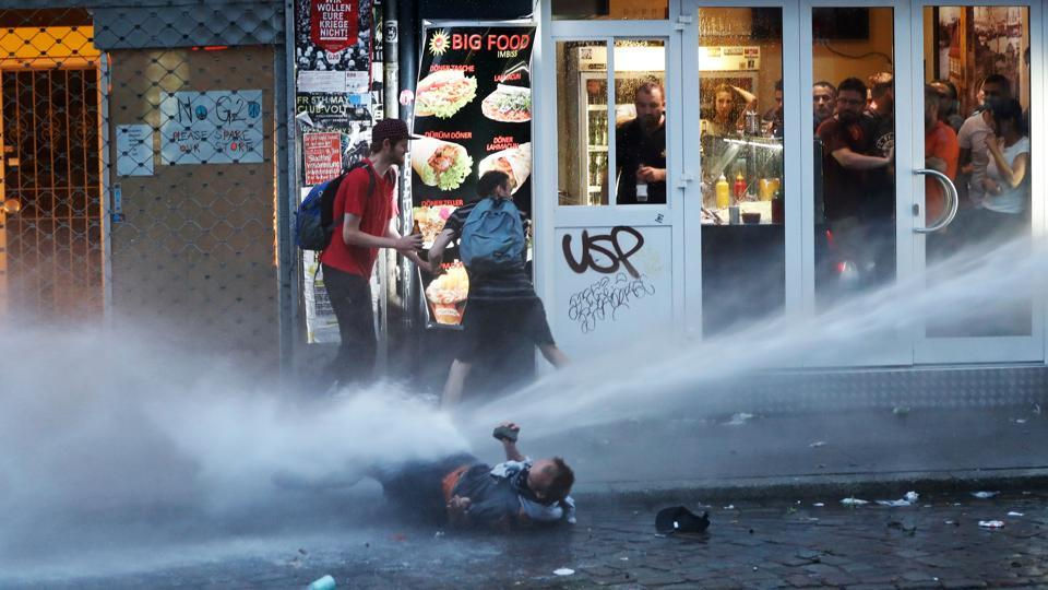 Riot police use water cannon against protesters in Hamburg.Heavily armed police commandos moved in after activists had spent much of the day attempting to wrest control of the streets from more than 15,000 police, setting fires, looting and building barricades. Police said 200 officers had been injured, 134 protesters temporarily detained and another 100 taken into custody. (AFP)