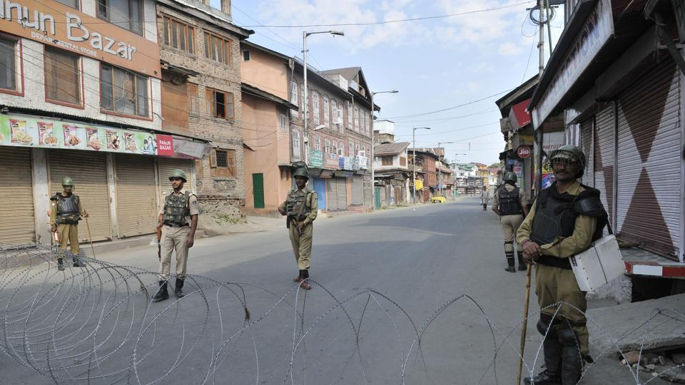 Paramilitary soldiers stand guard during curfew in downtown area of Srinagar on Saturday. The restrictions were lifted on Sunday.