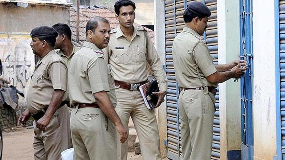 Policemen stand outside a house in Khagragarh,, Burdwan in October 2014.