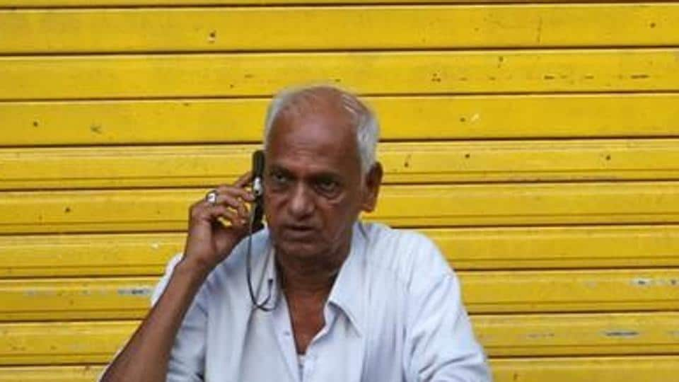 A man speaks on his mobile phone as he sits in front of a shop.