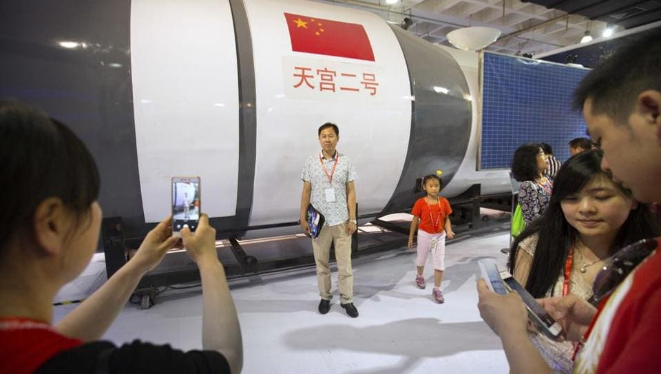 Visitors pose for photos in front of a full-size replica of China's Tiangong-2 space station at the China Beijing International High-Tech Expo in Beijing, Saturday, June 10, 2017.