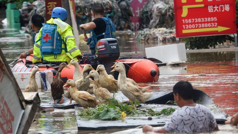 Rescue workers help people on a flooded street in Hunan province, China. Over 1.62 million people have been relocated across the province.