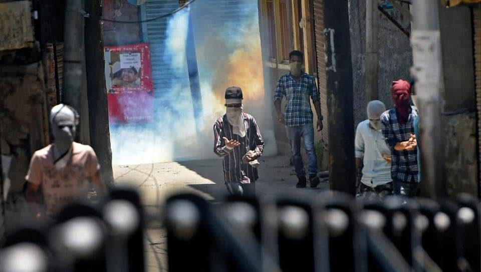 Protesters throw stones at security forces amid bursting of tear gas shell during clashes between security forces and protesters on the first death anniversary of Hizbul Mujahideen commander Burhan Wani, in Srinagar on July 8.