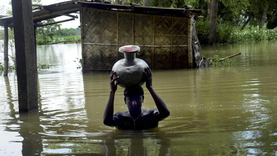 A boy carries fresh drinking water on head as he wades through flooded water at Padder parr village in Karimganj district, Assam on Friday.