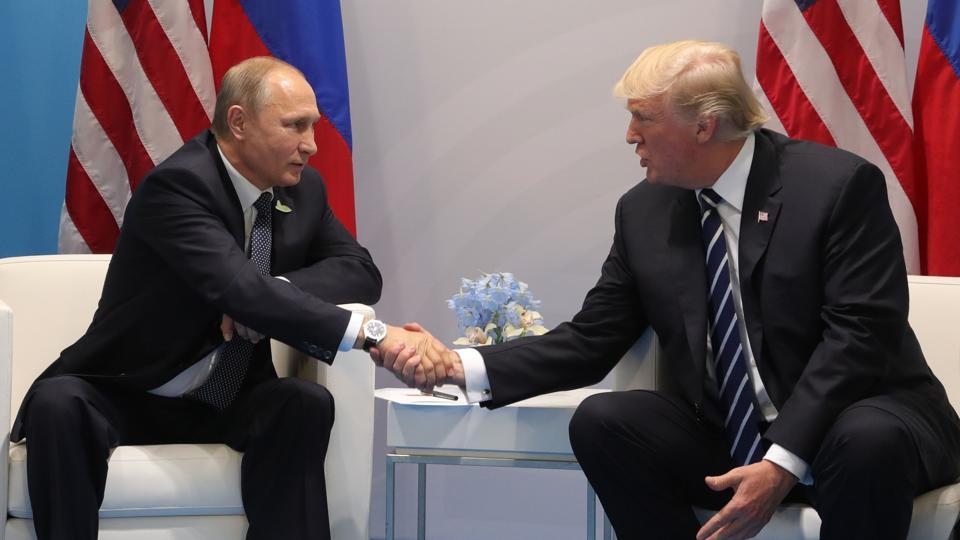 US President Donald Trump (R) and Russia's President Vladimir Putin shake hands as they hold a meeting on the sidelines of the G20 Summit in Hamburg, Germany, on July 7, 2017. Leaders of the world's top economies will gather from July 7 to 8, 2017 in Germany for likely the stormiest G20 summit in years, with disagreements ranging from wars to climate change and global trade. / AFP PHOTO / SPUTNIK / Mikhail KLIMENTIEV