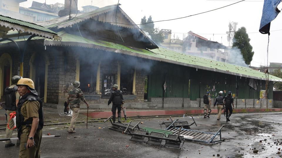 Policemen near a burning railway station on Saturday during an indefinite strike called by the Gorkha Janamukti Morcha (GJM) in Darjeeling.