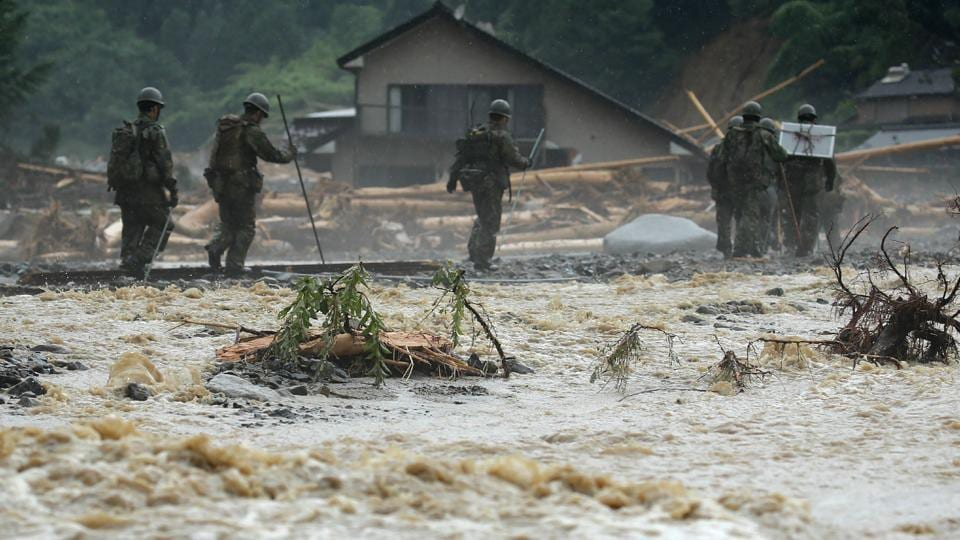 Defense forces soldiers walk beside a river during a search operation for missing people in a flooded area in Asakura on July 9, 2017.