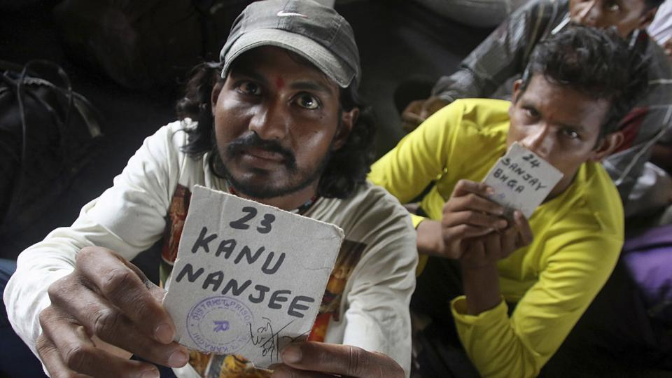 Indian fishermen show their name tags while they wait to board a train following their release from the central jail in Karachi on Sunday.