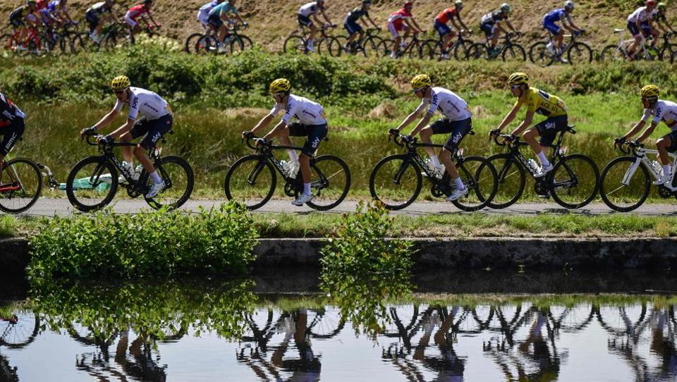 (From L) Great Britain's Luke Rowe, Poland's Michal Kwiatkowski, Great Britain's Christopher Froome, Great Britain's Geraint Thomas wearing the overall leader's yellow jersey and Colombia's Sergio Henao are reflected on a lake as they ride during the 160,5 km fifth stage of the 104th edition of the Tour de France cycling race.  (AFP)
