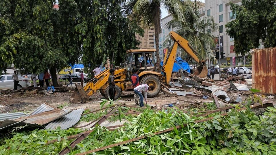 Workers demolish structures on New Linking Road.