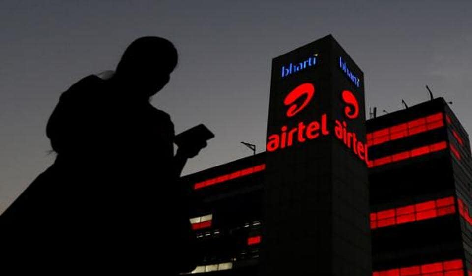 A girl checks her mobile phone as she walks past the Bharti Airtel office building in Gurgaon.