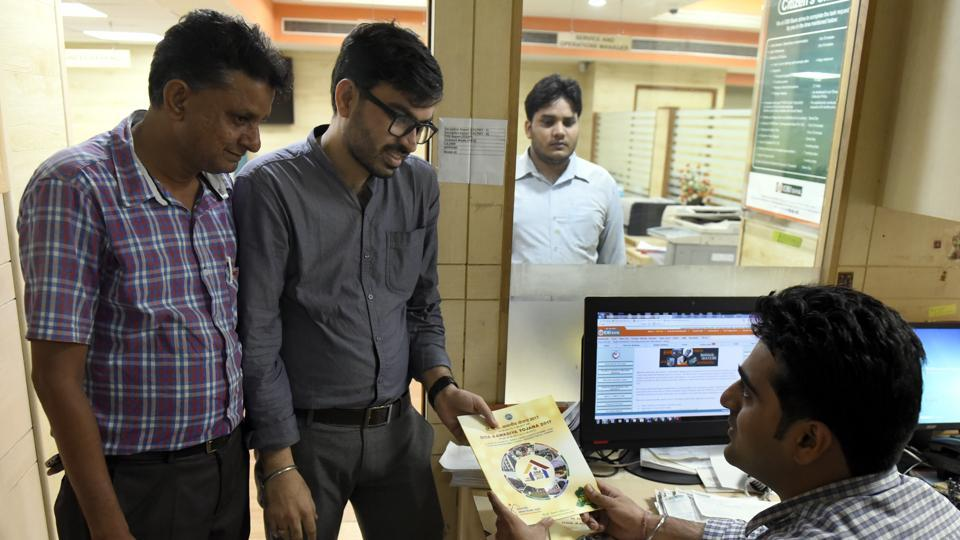 People buy the application form for DDA 2017 housing scheme at a bank counter on KG Marg in New Delhi. The DDA is offering 13,000 flats in its latest housing scheme.