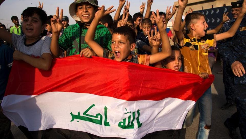 children holding Iraq's national flag react as Iraqi forces celebrate in the Old City of Mosul on July 9, 2017 after the government's announcement of the
