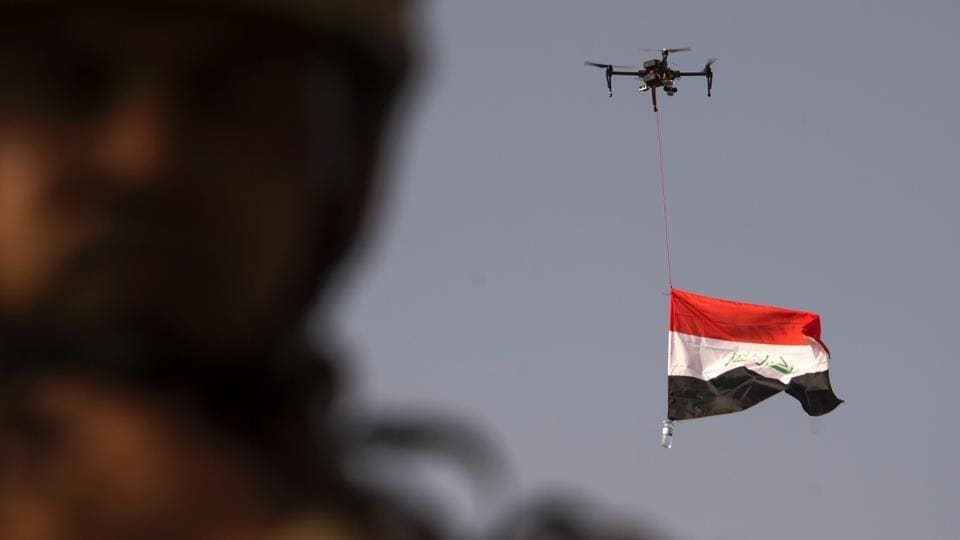 Iraq's national flag is suspended to a drone of Iraq's federal police as forces celebrate in the Old City of Mosul. (FADEL SENNA / AFP)