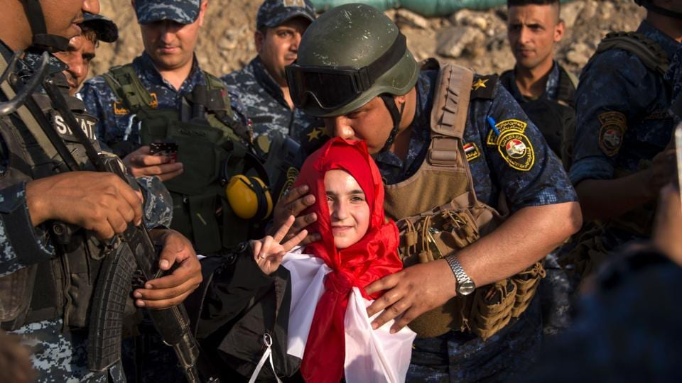 A member of Iraq's federal police kisses a girl as forces celebrate in the Old City of Mosul . The victory marked the formal end of a bloody battle that lasted nearly nine months, left much of Iraq's second-largest city in ruins, killed thousands of people and displaced nearly a million more. (FADEL SENNA / AFP)