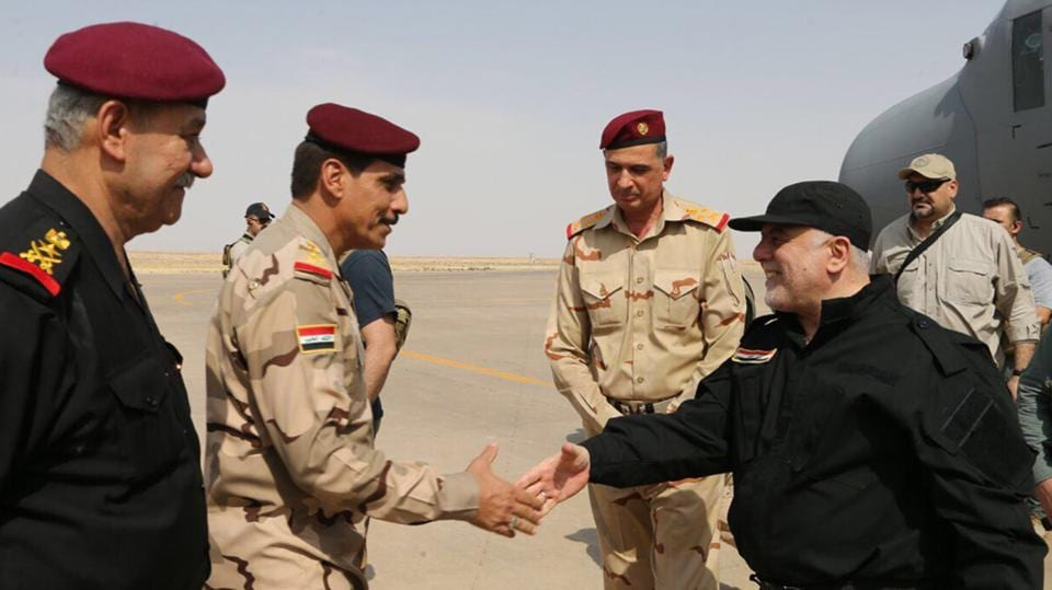 Iraqi Prime Minister Haider al-Abadi (R) shaking hands with police and army officers upon his arrival in Mosul. (AFP)