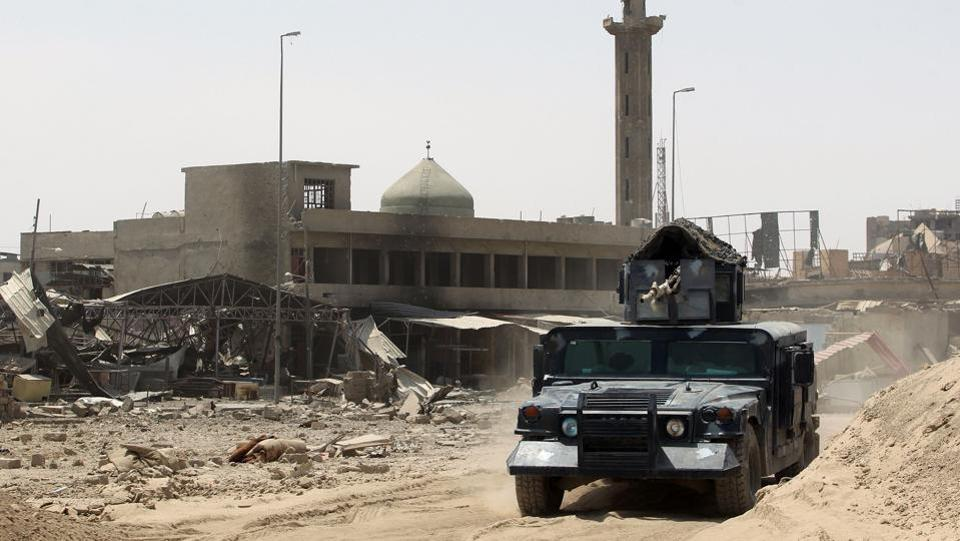 Iraqi forces drive their vehicle past a mosque in Mosul's Old City. The nearly nine-month battle for Mosul has ruined parts of the city, killed thousands of civilians and displaced nearly one million. (AHMAD AL-RUBAYE / AFP)