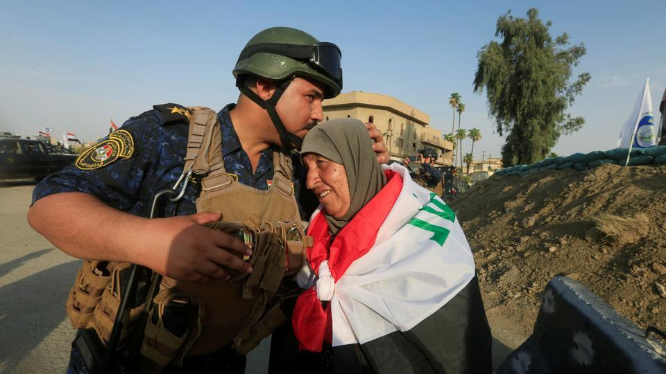 A member of Iraqi Federal police kisses an old woman in West Mosul, Iraq. (Alaa Al-Marjani / REUTERS)