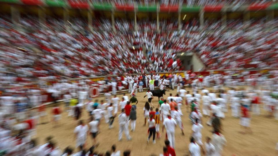 Revelers dodge a wild cow in the bull ring following at the San Fermin festival. The festival has religious origins, dating back to the Middle Ages.  (Eloy Alonso / REUTERS)