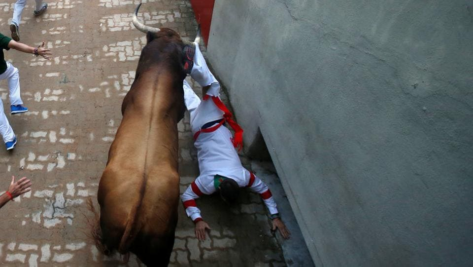A runner is dragged by the horns of a Puerto de San Lorenzo bull at the entrance to the bullring. (Joseba Etxaburu/ REUTERS)