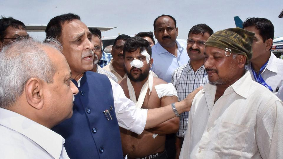 Gujarat chief minister Vijay Rupani interacts with the driver (right) of the bus that was attacked by the militants in J-K.