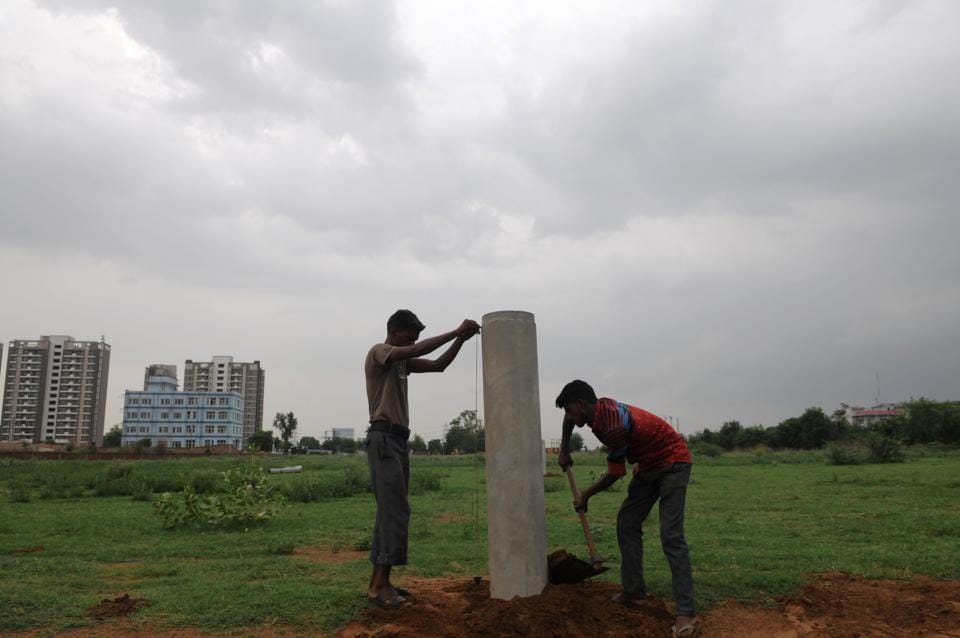 Workers mark land for the bypass road to connect Southern Peripheral Road near Sector 75 with NH8 beyond Kherki Daula toll.