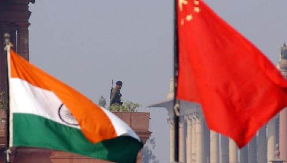 File photo of an Indian paramilitary trooper framed by Indian and Chinese flags near the presidential palace in New Delhi in January 2002.