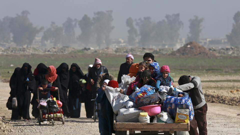 FILE - In this March 9, 2017 file photo, Iraqi civilians walk toward Iraqi security forces after fleeing their homes due to fighting between government forces and Islamic State militants, on the western side of Mosul, Iraq.