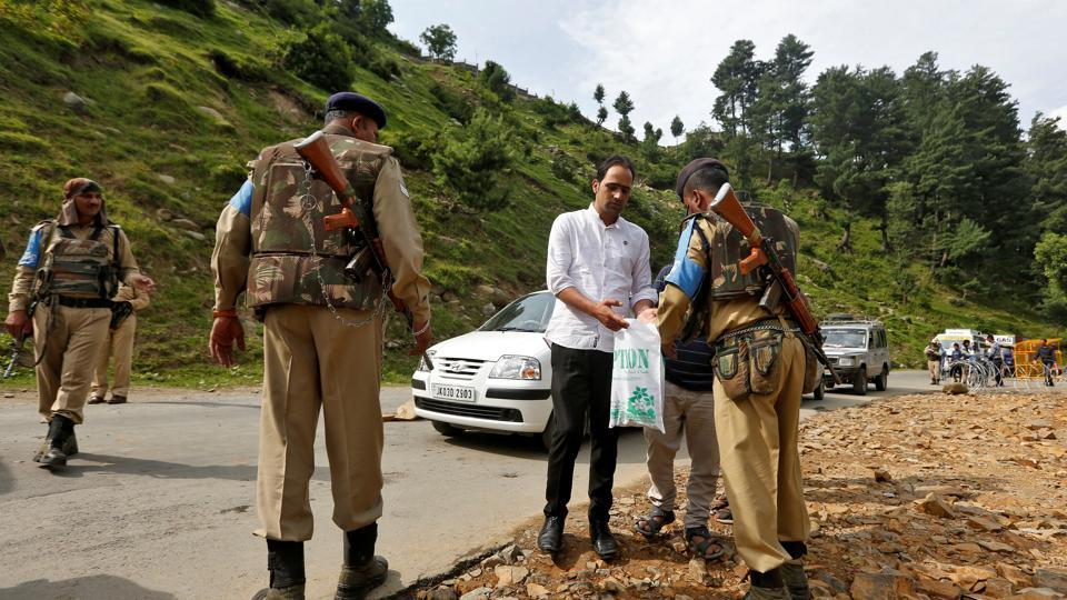 Security force personnel (R) check the bag of a man near a base camp of Hindu pilgrimage to the cave of Amarnath after seven pilgrims were killed in a gunbattle between Indian police and militants on Monday.