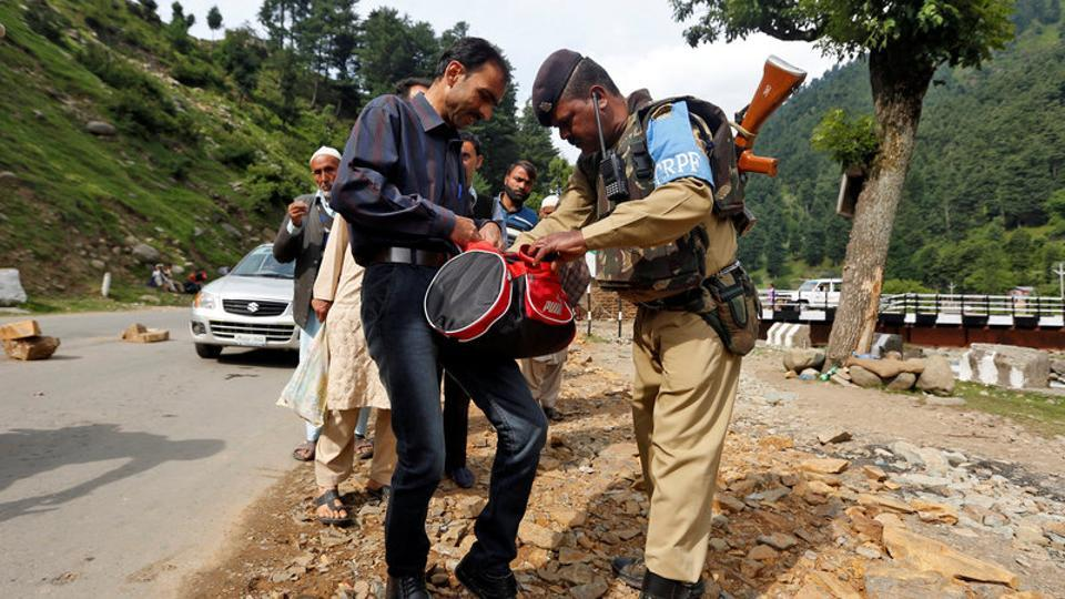 A security force personnel (right) checks the bag of a man near the base camp of Amarnath, in Langanbal village, south Kashmir's Anantnag district.