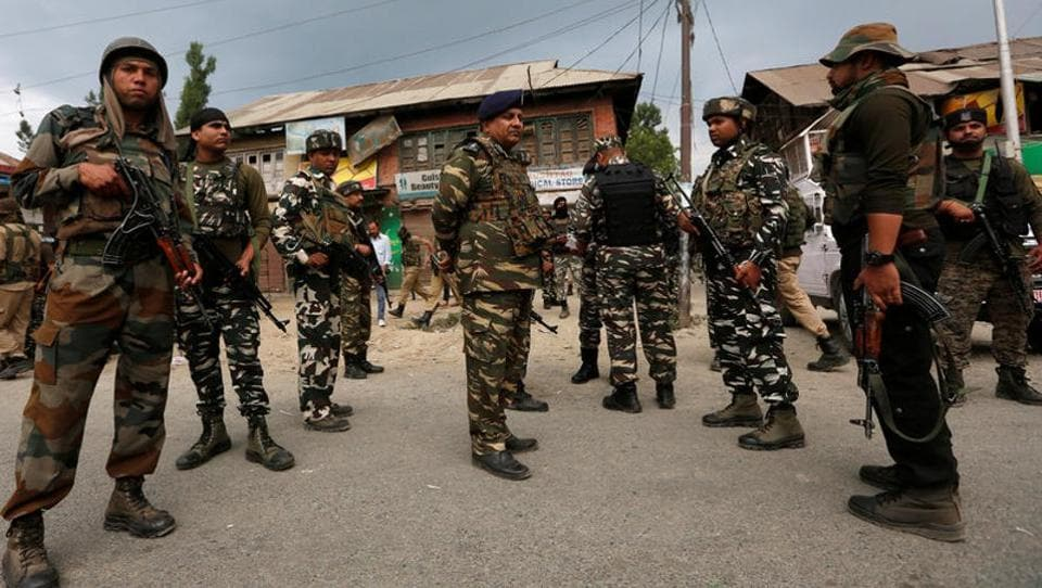 Security force personnel stand at the site of a gunbattle between police and militants on Monday in which seven pilgrims were killed, in Boateng village in south Kashmir's Anantnag district.