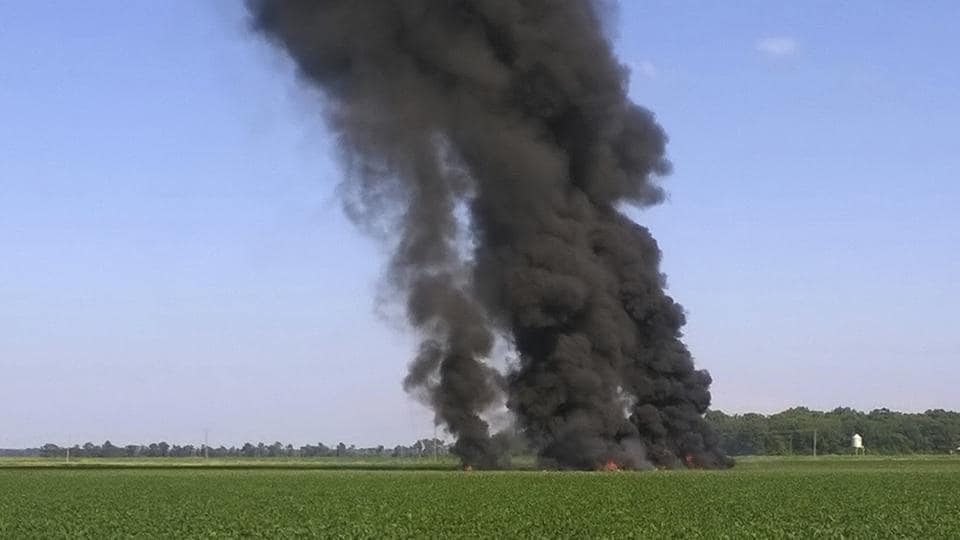 Smoke and flames rise from the wreckage after a military transport airplane crashed in a field near Itta Bena, Mississippi.