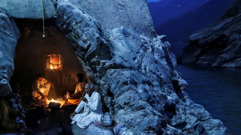 Priests sit inside a cave as they perform evening prayers on the banks of the river Ganga in Devprayag, Uttarakhand, the location of the confluence and renaming of two rivers into Ganga. (Danish Siddiqui / Reuters)