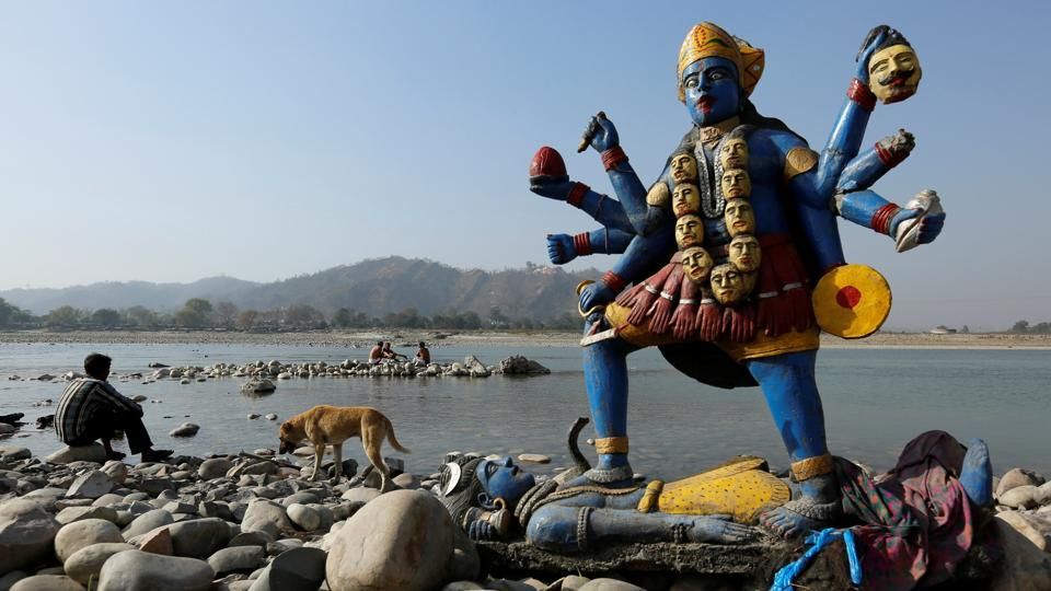 A man sits next to a damaged idol of the goddess Kali which was taken out after its immersion in the river Ganga in Haridwar, Uttarakhand. (Danish Siddiqui / Reuters)