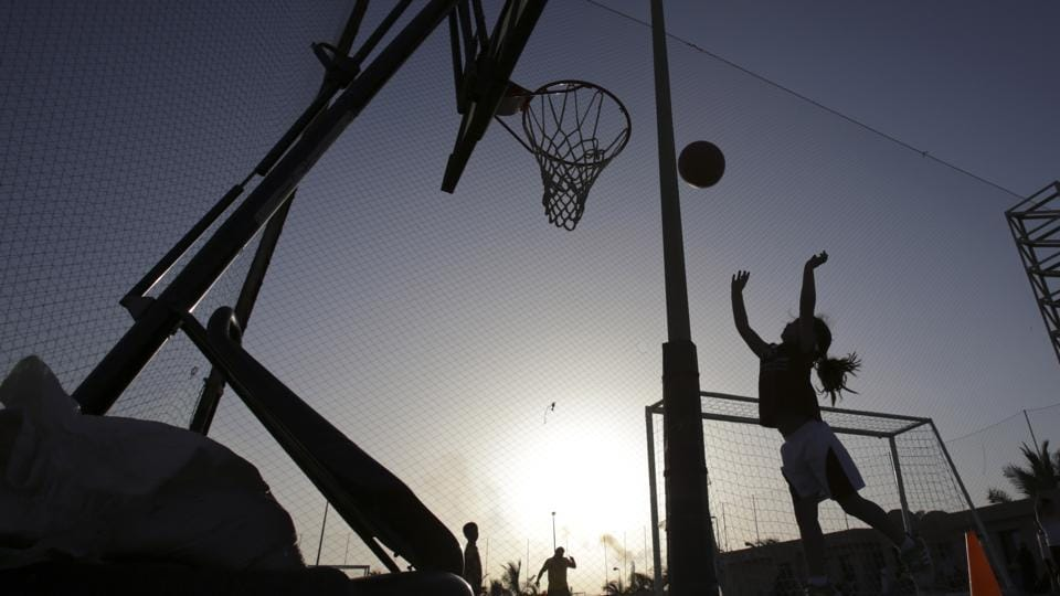 A girl shoots baskets during team practice at a private sports club in Jiddah, Saudi Arabia.