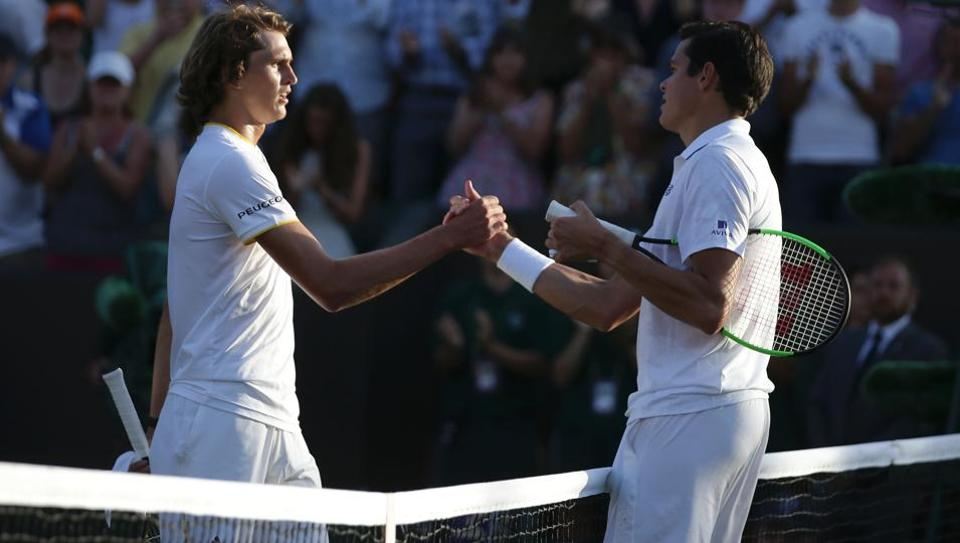 Canada's Milos Raonic (R) shakes hands at the net with Germany's Alexander Zverev (L) after Raonic won their men's singles fourth round match on the seventh day of the 2017 Wimbledon Championships.