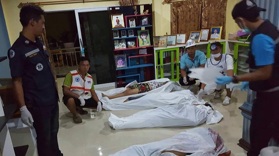 Rescue workers stand beside the bodies of victims of a shooting at a residence in the southern Thai province of Krabi.