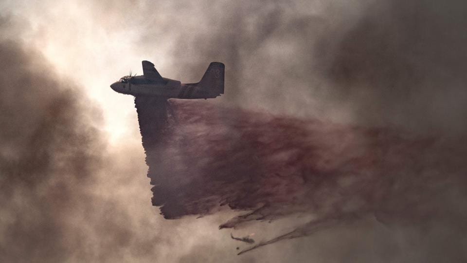 A plane drops fire retardant on an 80 acre spot fire that broke out in Butte County, California .  (JOSH EDELSON / AFP)