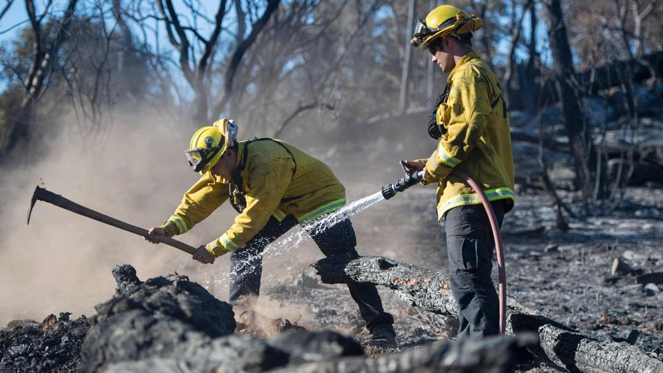 Bryce Briare (R) and Mike Manibusan (L) with the Marin County Fire Deptartment work on a smoldering hotspot as firefighters continue to build towards containment of the Wall fire in Oroville, California . (JOSH EDELSON / AFP)